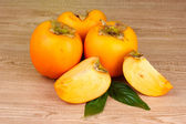 Appetizing persimmons on wooden background — Stock Photo