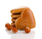 Heart-shaped cookies in stack with hazelnuts isolated on white — Stock Photo