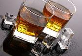 Två glas scotch whisky och is på grå bord — Stockfoto