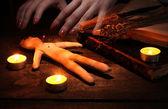 Menino boneco voodoo sobre uma mesa de madeira na luz de velas — Foto Stock