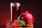 Ripe pomergranate and glass of juice on red background — Stock Photo