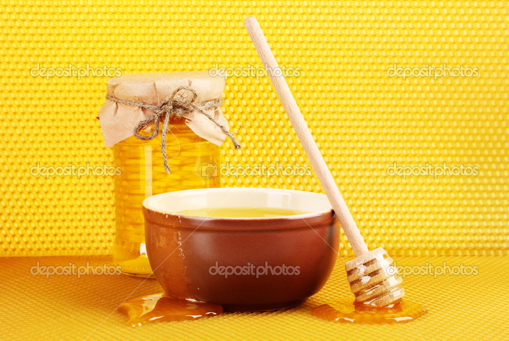 Jar of honey, bowl and wooden drizzler with honey on yellow honeycomb background — Stock Photo #9134933