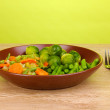 Mixed vegetables on plate on wooden table on green background — Stock Photo