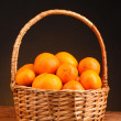 Tangerines in a beautiful basket on wooden table on brown background - Foto de Stock