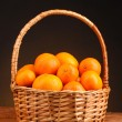 Tangerines in a beautiful basket on wooden table on brown background - Stock Photo