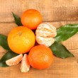 Tangerines with leaves on wooden table - Stock Photo
