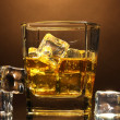 Glass of scotch whiskey and ice on brown background - Stock Photo