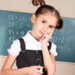 Beautiful little girl standing near blackboard in the classroom — Stock Photo #9169970