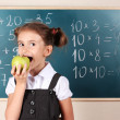 Beautiful little girl with apple standing near blackboard in classroom — Stock Photo #9169973