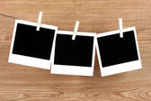 Photo papers hanging on the clothesline on wooden background — Stock Photo