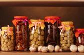 Deliciosos cogumelos marinados em frascos de vidro e cogumelos champignons crus — Foto Stock