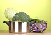 Saucepan with broccoli and cabbages on wooden table on green background — Stock Photo
