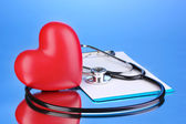 Medical stethoscope with clipboard and heart on blue background — Stock Photo