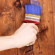 Painting wooden fence with yellow paint - Stock Photo