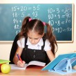 Stock Photo: Little schoolchild in classroom near blackboard