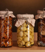Delicious marinated mushrooms in the glass jars on wooden shelfs — Stock Photo