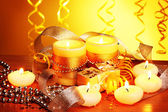 Beautiful candles, gifts and decor on wooden table on yellow background — Stock fotografie