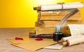 Staré knihy, svitky, peří pero a inkwell na dřevěný stůl na žlutém pozadí — Stock fotografie