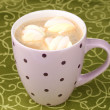 Cup of cappucino with marshmallows on green tablecloth — Stock Photo #9184921