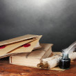 Old books, scrolls, feather pen and inkwell on wooden table on grey backgro — Stock Photo
