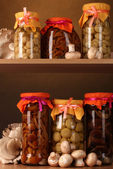 Delicious marinated mushrooms in the glass jars, raw champignons and oyster — Stock Photo