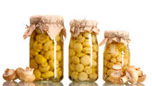 Delicious marinated mushrooms in the glass jars and raw champignons isolate — Stock Photo