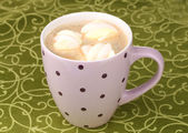 Cup of cappucino with marshmallows on green tablecloth — Stock Photo