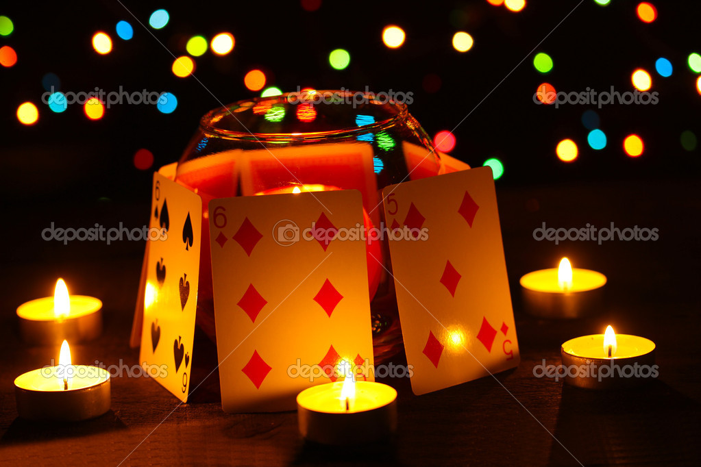 Candles and playing cards on wooden table on bright background — Stock Photo #9185003