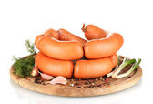Tasty sausages on wooden board and spices isolation on white — Stock Photo