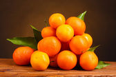 Tangerines with leaves on wooden table on brown background — Stock Photo