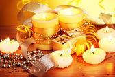 Velas bonitas, presentes e decoração na mesa de madeira em fundo amarelo — Foto Stock