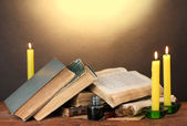 Old books, scrolls, ink pen inkwell and candles on wooden table on brown ba — Stock Photo