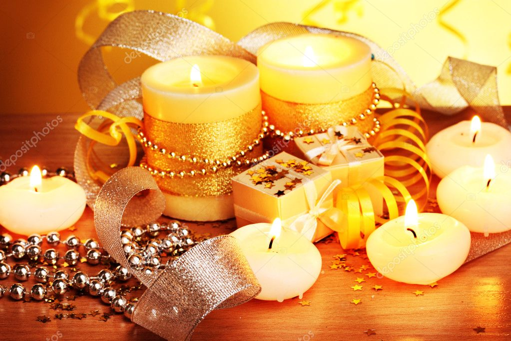 Beautiful candles, gifts and decor on wooden table on yellow background — Stock Photo #9197919