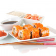 Stock Photo: Delicious sushi on plate, chopsticks, soy sauce, fish and shrimps isolated