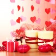Beautiful candles with romantic decor on a wooden table on a red background - Stock Photo