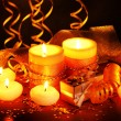 Beautiful candles, gifts and decor on wooden table on brown background - Stock Photo