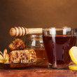 Honey, lemon, honeycomb and a cup of tea on wooden table on brown backgroun — Stock Photo