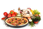 Delicious pizza on plate, vegetables and spices isolated on white — Stock Photo