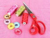 Scissors, buttons and bright threads on fabric isolated on white — Stock Photo