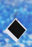 Photo on fish hook on blue background — Stock Photo