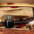 Old books, scrolls, ink pen and inkwell on wooden table on brown background — Stockfoto