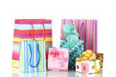 Bright gift bags and gifts isolated on white — Stock Photo