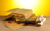 Old books, scrolls, ink pen and inkwell on wooden table on yellow backgroun — Foto de Stock