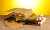 Libros antiguos, manuscritos, pluma de tinta y tintero en mesa de madera sobre fondo amarillo — Foto de Stock