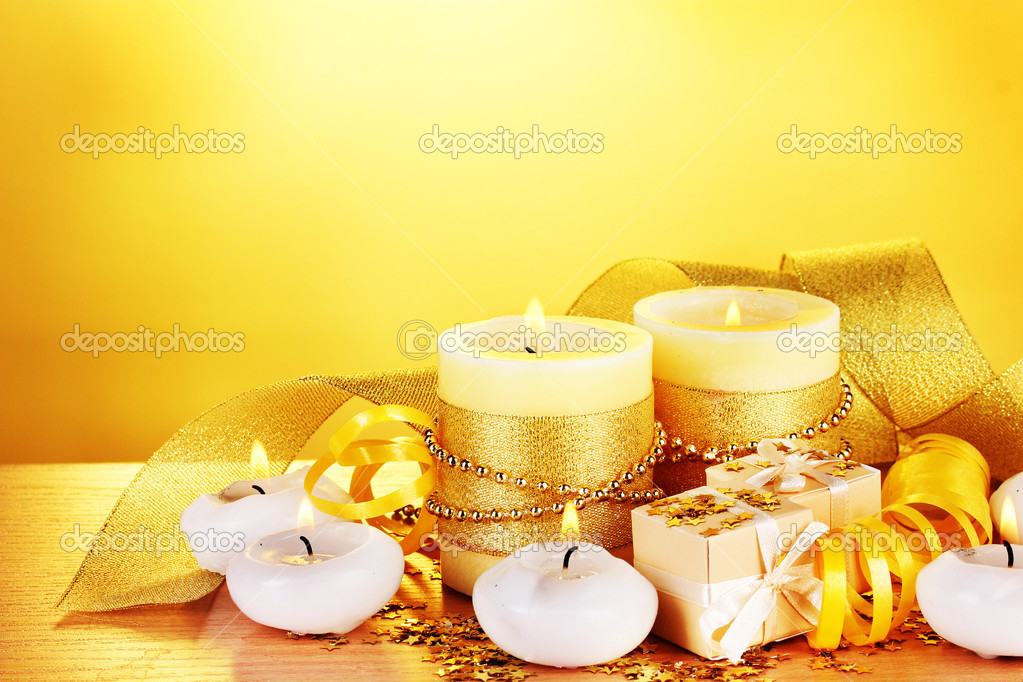 Beautiful candles, gifts and decor on wooden table on yellow background — Stock Photo #9244305