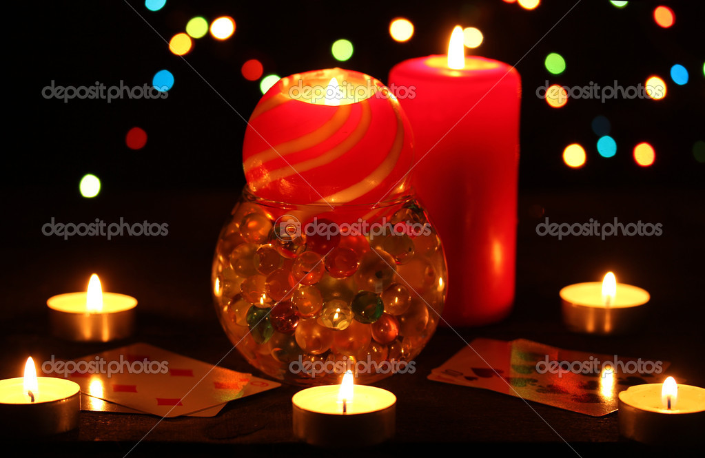 Candles and playing cards on wooden table on bright background — Stock Photo #9244577