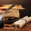 Old books, scrolls, feather pen and inkwell on wooden table on brown background — Stock Photo