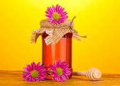 Sweet honey in jar with drizzler on wooden table on yellow background — Stock Photo
