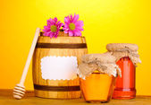 Sweet honey in jars and barrel with drizzler on wooden table on yellow background — Stock Photo