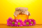 Sweet honey in jar on wooden table on yellow background — Stock Photo